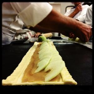 Bande de tarte aux pommes sur pâte feuilletée. La difficulté consiste notamment à placer les pommes presque droite, piquées sur le fond de compote.